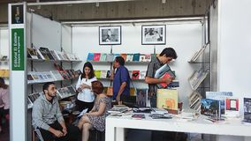 People looking at books at a book feria. At college. bookstore Stock Image