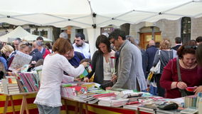 People looking books on street stalls in Saint George day stock video footage