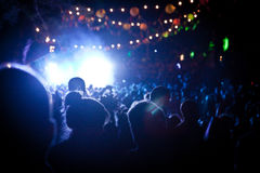 People looking at a festival stage at night with colour lighting. Peoples silhouettes facing a stage with white lights in a festival tent at night with orange Stock Photos