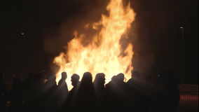 People looking at a fire easter 1080p. Large flames at night in 1080p stock footage