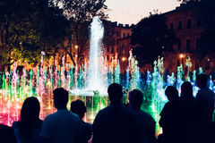 People looking at fountain and lights in the evening Stock Photography