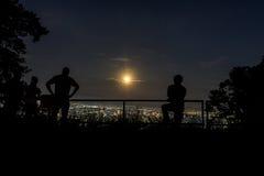 People looking at full moon raising up Stock Photo