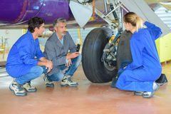 People looking at landing gear aircraft. People looking at the landing gear of an aircraft Royalty Free Stock Images