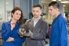 People looking at mechanical part. Mechanical stock photos