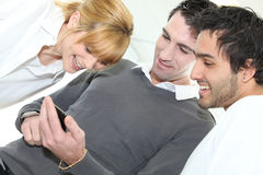 People looking at mobile telephone. Three people looking at mobile telephone screen Royalty Free Stock Photo