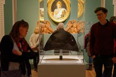 People looking at Napoleon`s hat in a museum royalty free stock photography