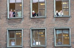 People Looking Out Multiple Windows Stock Photography