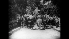 People looking at policemen accompanying horse cart on street stock video