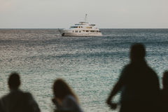People Looking at Sea. While a Nautical Vessel Passing Through Royalty Free Stock Photos