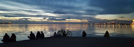 People looking at the sea. A picture of people relaxing and staring at a sea,in a sunset day afternoon in  a greek town thessaoniki Royalty Free Stock Photo