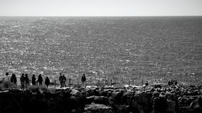People looking sea on rock formation. Blackandwhite photography horizon water sea And sky Royalty Free Stock Photos