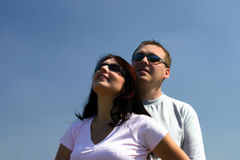 People - Looking up. A couple looking up. Blue sky as a background. Main focus is on the woman Royalty Free Stock Photos