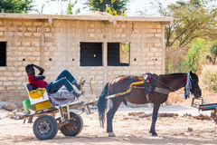 People in LOUGA, SENEGAL. LOUGA, SENEGAL - MAR 15, 2013: Unidentified Senegalese man sits in a horse carriage. People in Senegal suffer of poverty due to the royalty free stock photo