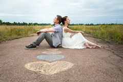 People in love. Wedding couple sitting on ground. love symbols on pavemant . hearts. people in love. happy bride and groom portraits. men and women sitting back Royalty Free Stock Photo