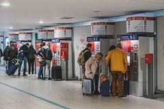 People with luggage buying train ticket at vending machine near airport in Berlin. Berlin, Germany - march 2019: People with luggage buying train ticket at royalty free stock image