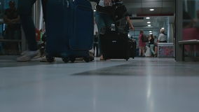 People with luggage coming out of the airport. Slow motion clip of people with luggage coming out of the opening doors of the airport. Scene with the crowd of stock footage