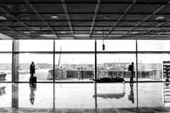 People with luggage waiting hall of airport at window glass. Frankfurt am Main, Germany-October 11, 2015: people or tourist passengers with suitcase and luggage Royalty Free Stock Photo