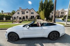 People luxury lifestyle concept. Young adult man driving convertible car in luxury houses neighborhood.  Royalty Free Stock Images
