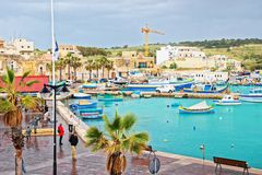People and Luzzu colorful boats at Marsaxlokk Harbor Malta Stock Photo