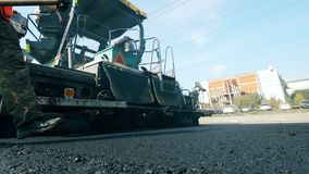 People and machines work on a road, laying asphalt.