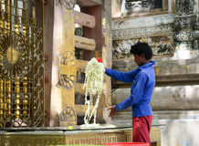 People at Mahabodhi Temple in Gaya, India. Bodh Gaya, India - Jul 9, 2015. A man working at Mahabodhi Temple Complex in Bodhgaya, India. The Mahabodhi Vihar, a Stock Image