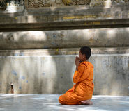 People at Mahabodhi Temple in Gaya, India. A novice monk praying at Mahabodhi Temple Complex in Bodhgaya, India. The Mahabodhi Vihar, a UNESCO World Heritage Stock Photos