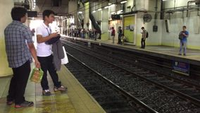 People at the Makati station in Manila. People standing and waiting for the train at the Makati station in Manila, Philippines stock footage