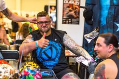 People make a tattoos at the 10-th International Tattoo Convention in the Congress-EXPO Center. KRAKOW, POLAND - JUNE 6, 2015: People make a tattoos at the 10 royalty free stock images
