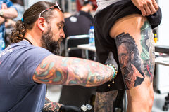 People make a tattoos at the 10-th International Tattoo Convention in the Congress-EXPO Center. KRAKOW, POLAND - JUNE 6, 2015: People make a tattoos at the 10-th stock photo