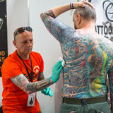 People make a tattoos at the 10-th International Tattoo Convention in the Congress-EXPO Center. KRAKOW, POLAND - JUNE 6, 2015: People make a tattoos at the 10 royalty free stock image