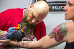 People make a tattoos at the 10-th International Tattoo Convention in the Congress-EXPO Center. Royalty Free Stock Photo