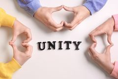 People making heart shape symbols. With hands and word UNITY on white background royalty free stock photography