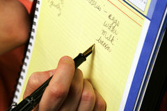 People Making List, Hand Holding Pen. Hand Holding Ink Pen and Writing List stock photo