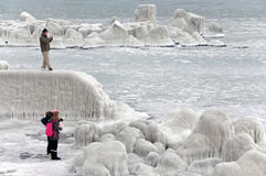 People making photos near frozen sea coastline Stock Photos