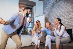 People making team training exercise during team building seminar singing karaoke. Indoor team building activities. Business people making team training exercise stock photography