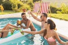 People making a toast at a poolside party stock image