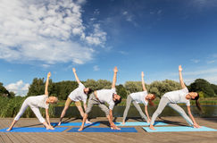 People making yoga in left triangle pose outdoors Stock Photography