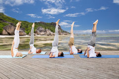 People making yoga in shoulderstand pose on mat Royalty Free Stock Images