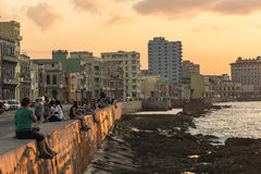 People Malecon boardwalk sunset Havana. People sitting on the wall at Malecon boardwalk in sunset, Havana, Cuba. Citizens of Havana is called Habaneros in Stock Images