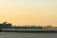 People at Malecon in sunset Havana. People at Castillo de San Salvador de la Punta and Malecon in sunset, Havana, Cuba Stock Images