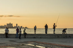 People at Malecon in sunset Havana. People at Malecon in sunset, Havana, Cuba. Citizens of Havana is called Habaneros in Spanish Stock Photo