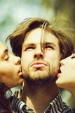 People, man getting kiss by two adorable girls. Kiss. people, men or bearded macho with beard getting kiss by two adorable girls or cute women on sunny day on royalty free stock photography