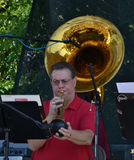 People-Man playing Trumpet. People-Male Musician playing trumpet with Tuba in the Background Stock Photo
