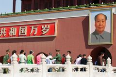 People and Mao Zedong portrait. Crowd of people helped by policemen in uniform while entering the forbiden city in Beijing, China, with picture of president Mao Royalty Free Stock Photos