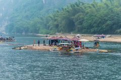 People, market places and a boats on a small island on the Li ri. Yangshuo, China - October 20, 2013: People, market places and bamboo rafts on a small island on Stock Photo