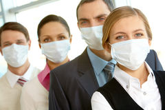 People in masks. Pretty female in protective mask looking at camera on background of business people stock images