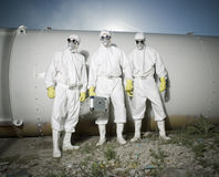 People with masks. Three people with masks standing in front of a big metal tube Stock Image