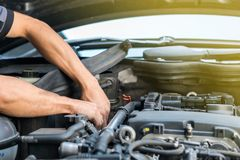 People or mechanic car repair during investigate cause of problem mechanism check or working on automobile gasoline or diesel. Engine at garage stock images