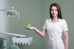 young female dentist with green apple in hand on background of medical office royalty free stock photos