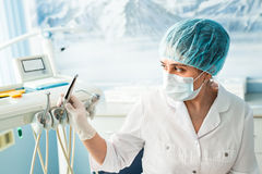 People, medicine, stomatology and healthcare concept - happy young female dentist with tools over medical office. Background Stock Photos